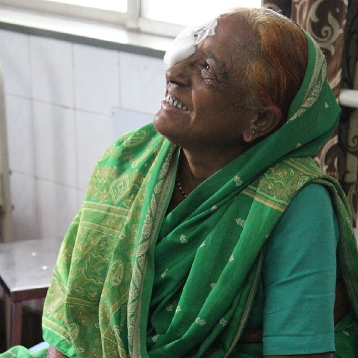 An elderly Indian woman wearing a green sari looks up after the removal of a cataract, an eye patch on her right eye