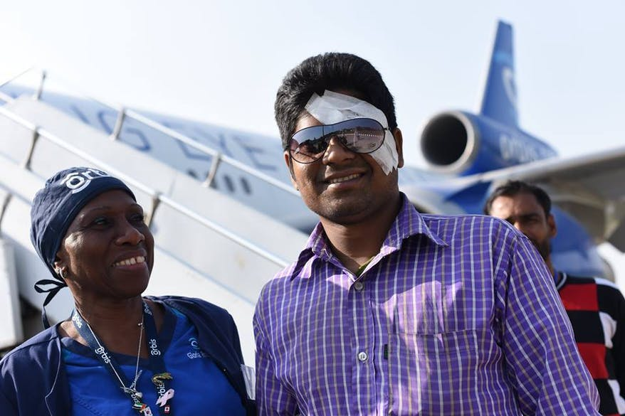 Patient Rabiul from Bangladesh stands with a nurse in front of the Flying Eye Hospital