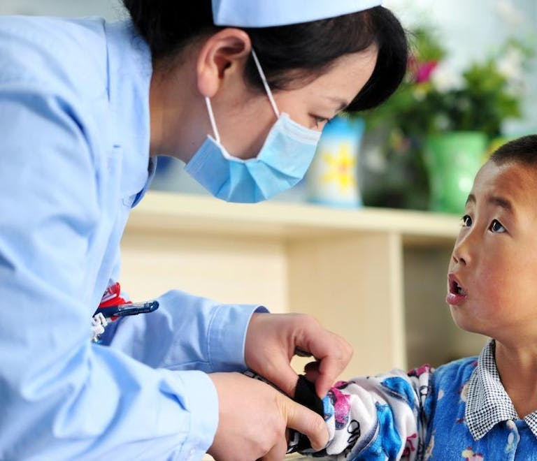 A young Chinese patient is attended to by a nurse dressed in scrubs