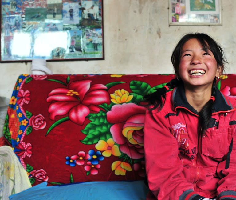 Young girl smiling on a sofa.