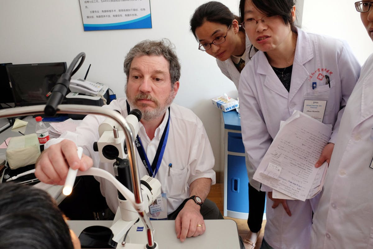 Dr James Brandt and colleagues assessing results of an eye scan on glaucoma patient Shunwen