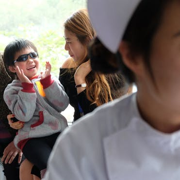 A nurse in a white cap and smock looks off to the right as a group of children and parents waiting to be seen talk behind her