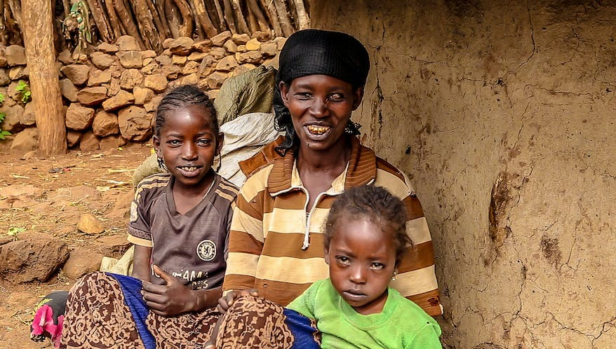 Trachoma patient Aylito, Ethiopia, hugs two of her children, grinning at the camera