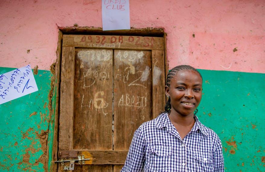Ethiopian schoolteacher Banchi standing by a door