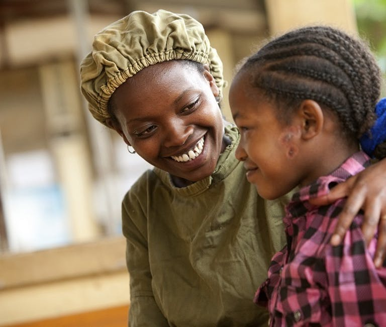 Trachoma patient Asegedech, wearing a pink checked shirt, is hugged by Integrated Eye Care worker Tsehay