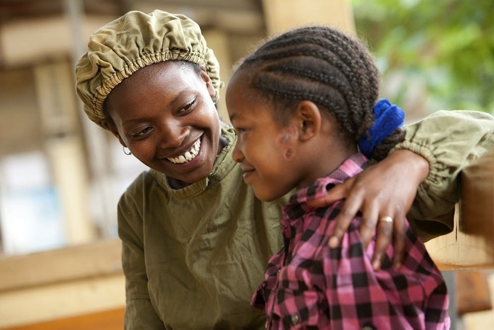 Health clinic nurse comforts young patient.