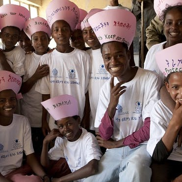 Children wearing pink hats and white shirts perform a song about trachoma prevention in Ethiopia