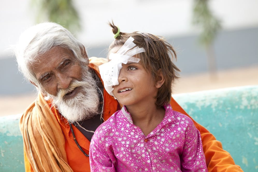 A grandfather in orange with his granddaughter, post surgery, in pink. She is wearing an eye patch
