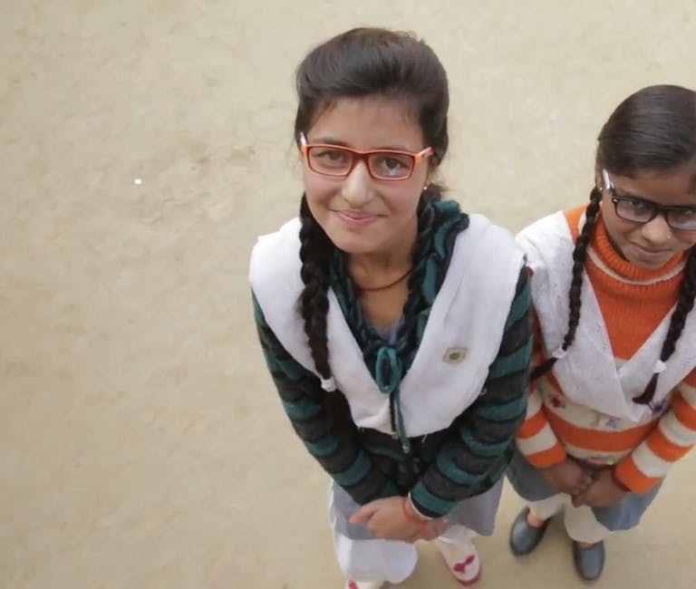 Two girls stare cheekily at the camera, both wearing glasses