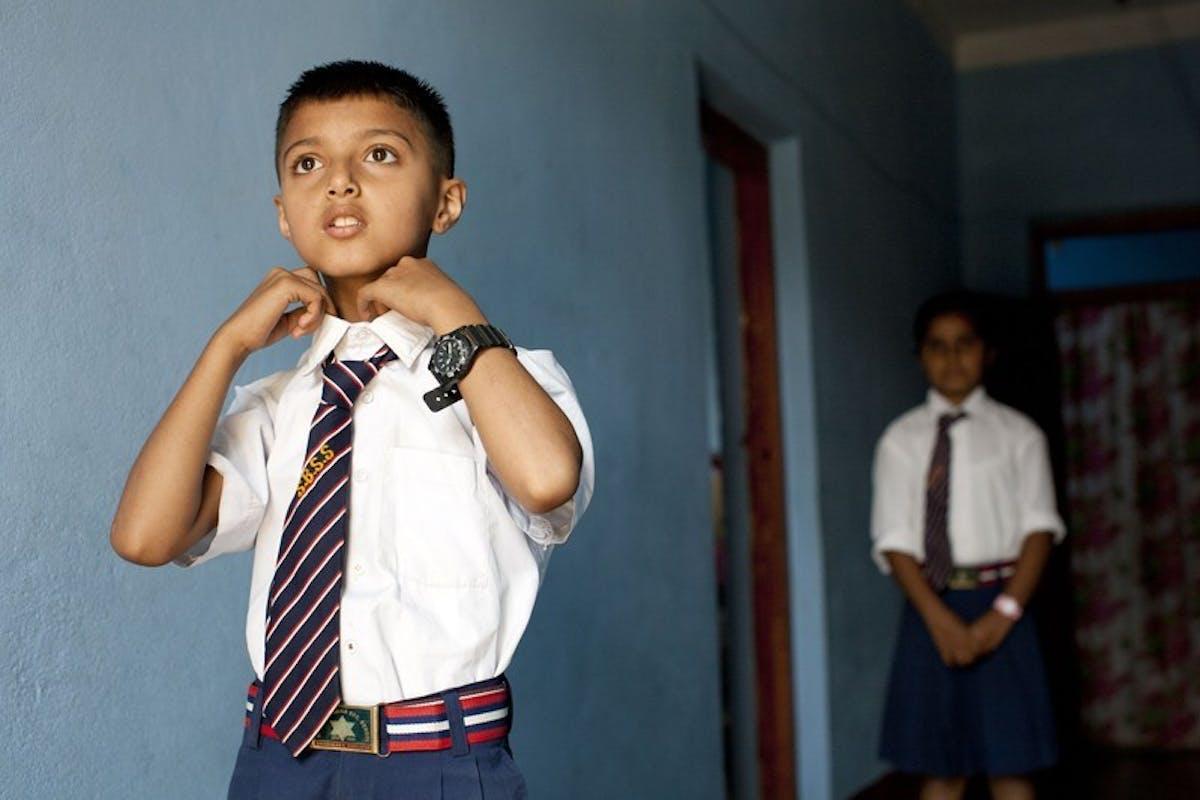 Young boy doing up his school tie.