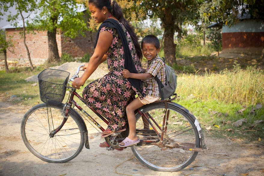 Nepalese paediatric patient Krish on the back of his mother's bicycle, laughing and clinging to her skirt