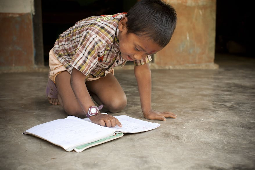 Paediatric Nepalese patient Krish reads a book on the floor