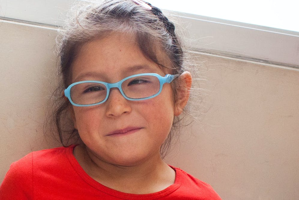 Paediatric patient Erika from Peru, wearing blue glasses and a red top