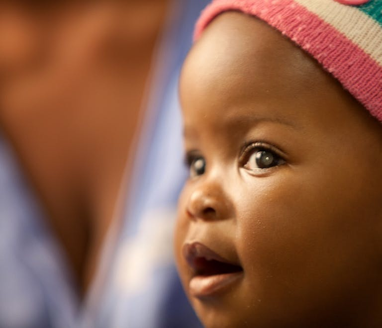 A young South African child with retinoblastoma, wearing a multicoloured hat