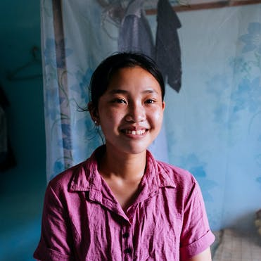 Trinh, strabismus patient from Vietnam, wearing a pink shirt