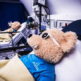 In the Flying Eye Hospital recovery room, Seymour the teddy bear lies propped up in bed