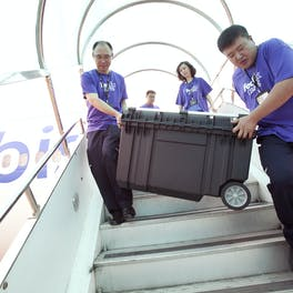 Male volunteers in purple FedEx shirts carry luggage from the Orbis Flying Eye Hospital