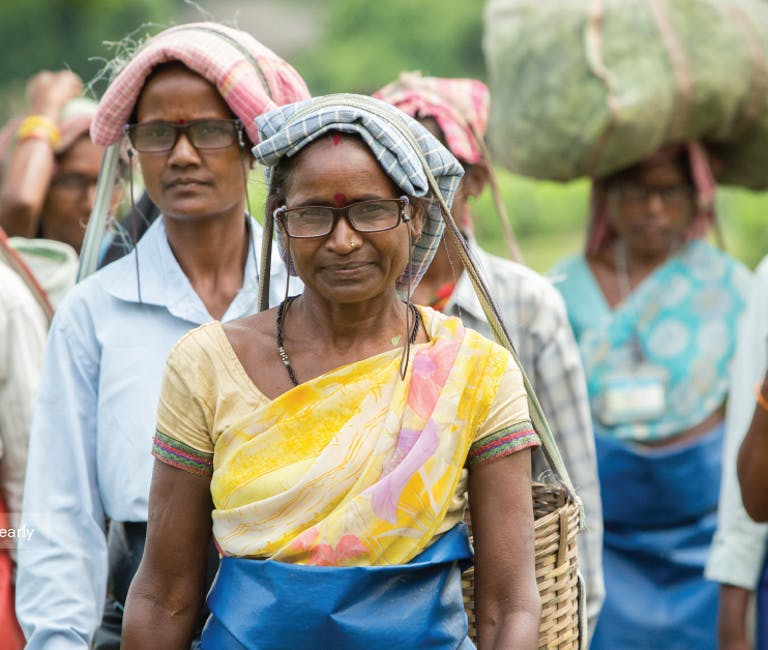 Local women walk along, carrying various items on their heads