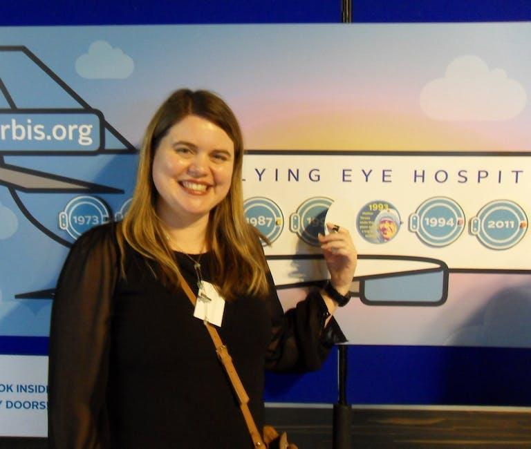 Volunteer Polly Holt stands in front of a Flying Eye Hospital timeline