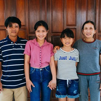Trinh standing with her family following her sight-saving operation