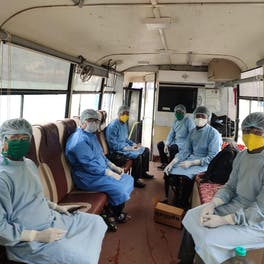 Maintaining Social distance: Patients waiting for their turn and team of doctors in Vision Van