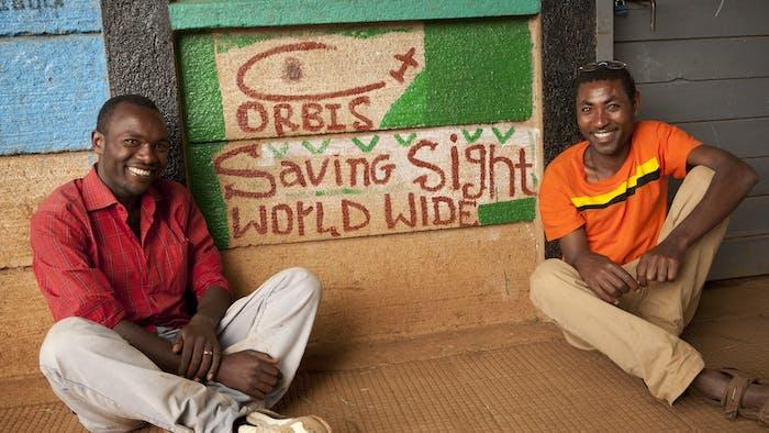 Men in front of Orbis saving sight worldwide logo.