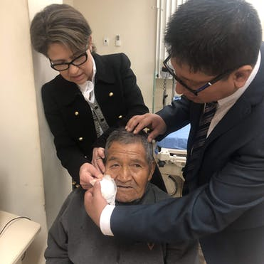 Dr. Laura Wayman and trainee Dr. De La Cruz removing bandages from a cataract patient in Peru post-surgery