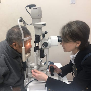 Orbis Volunteer Faculty Dr. Laura Wayman screening a cataract patient in Peru post-surgery