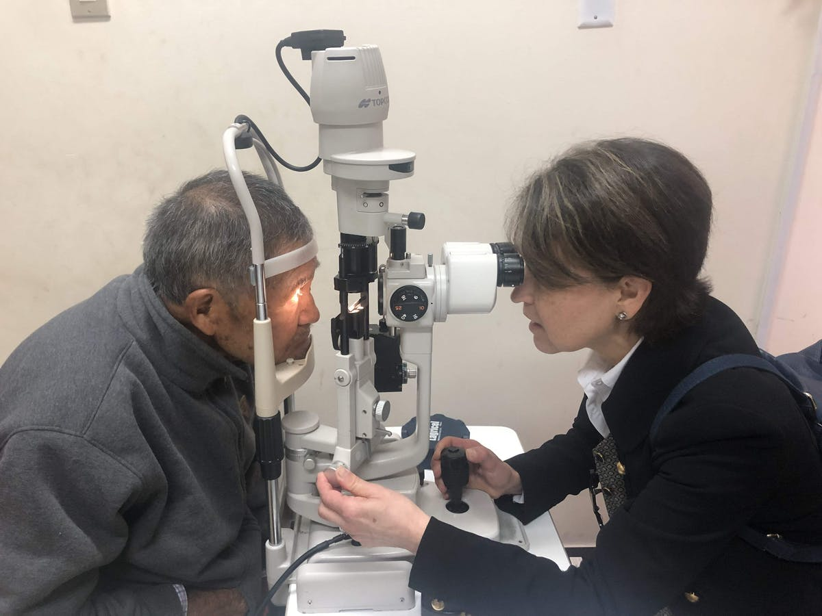 Orbis Volunteer Faculty Dr. Laura Wayman screening a cataract patient in Peru post-surgery