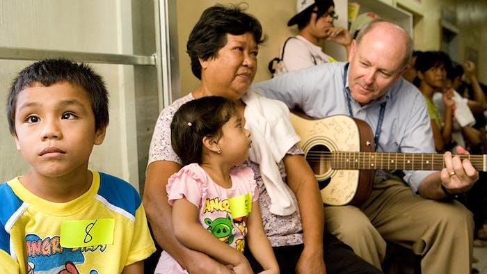 Flying Eye Hospital pilot Captain Gary Dyson calms children awaiting surgery with his impressive guitar skills