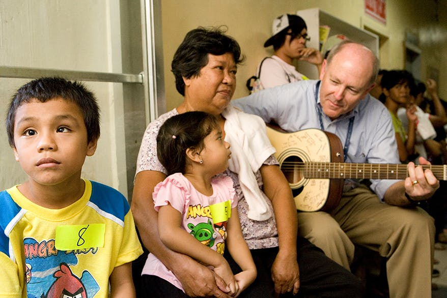Flying Eye Hospital pilot Captain Gary Dyson calms children awaiting surgery with his impressive guitar skills