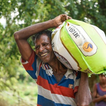 A volunteer from Akhand Jyoti in Bihar, India, delivering food packages