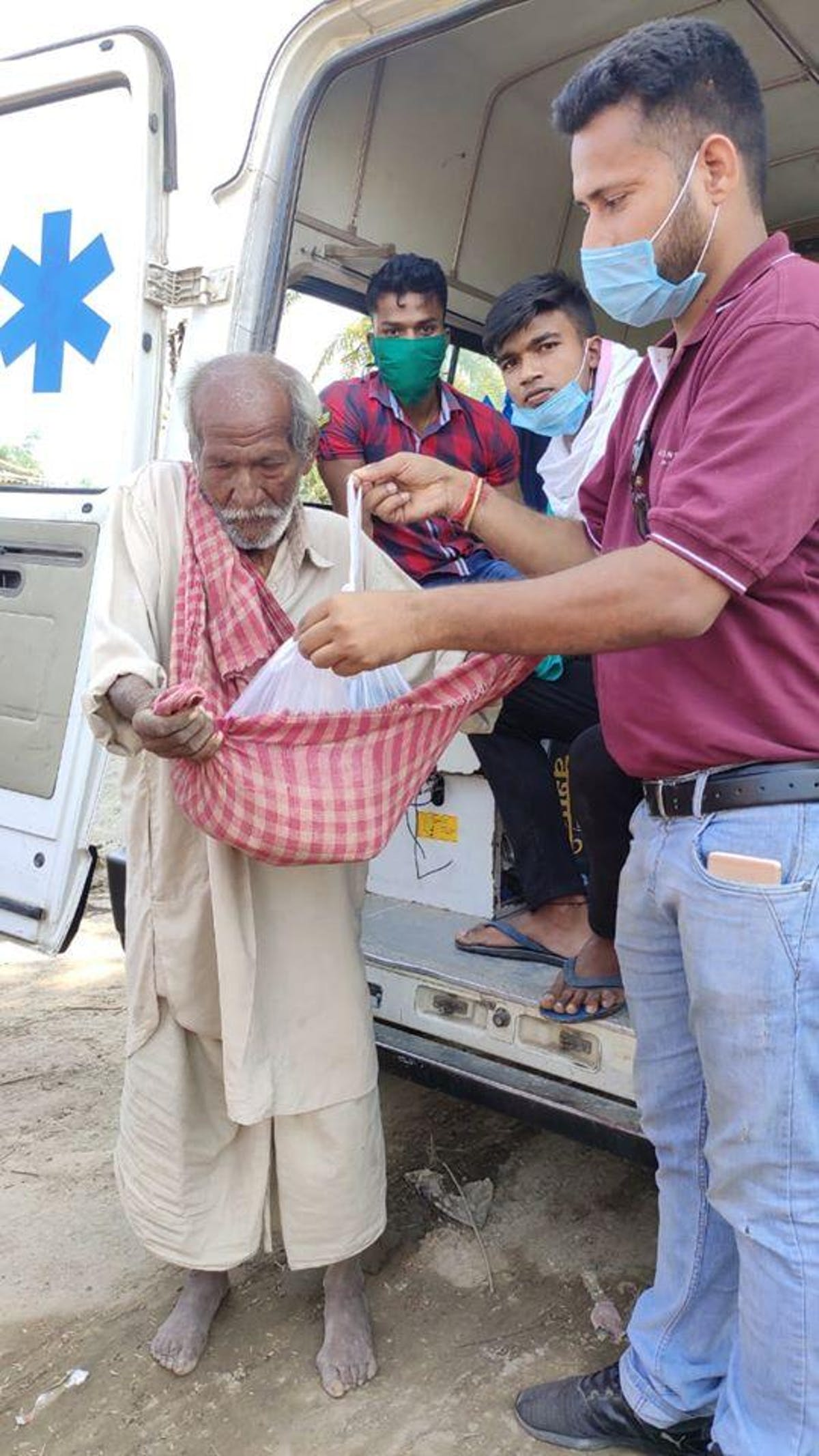 A man accepts a food package from the team at Akhand Jyoti Eye Hospital in Bihar, India