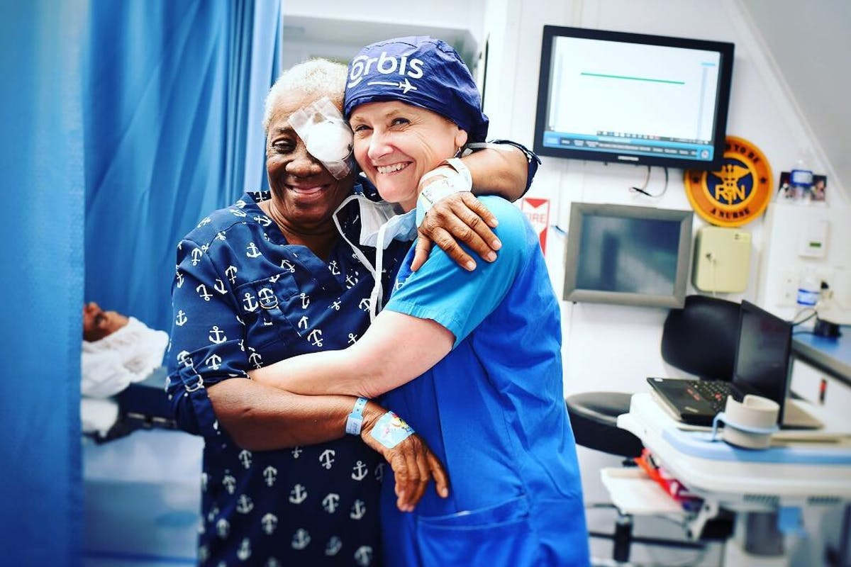 Orbis Flying Eye Hospital Jamaica: A happy patient hugs our Volunteer Faculty following cataract surgery