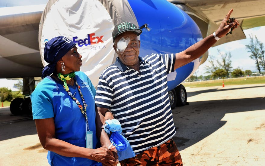 Orbis Flying Eye Hospital Jamaica cataract patient Denzil leaving the plane assisted by Nurse Gloria