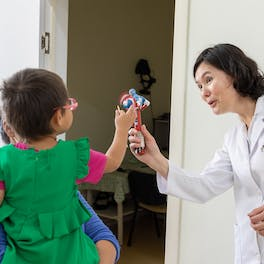 Marla plays with a toy held up by Dr. Murat