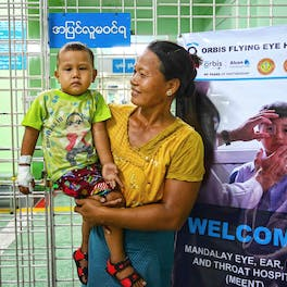 A mother and her son wait to be seen by Orbis volunteer faculty on screening day during Myanmar Flying Eye Hospital project