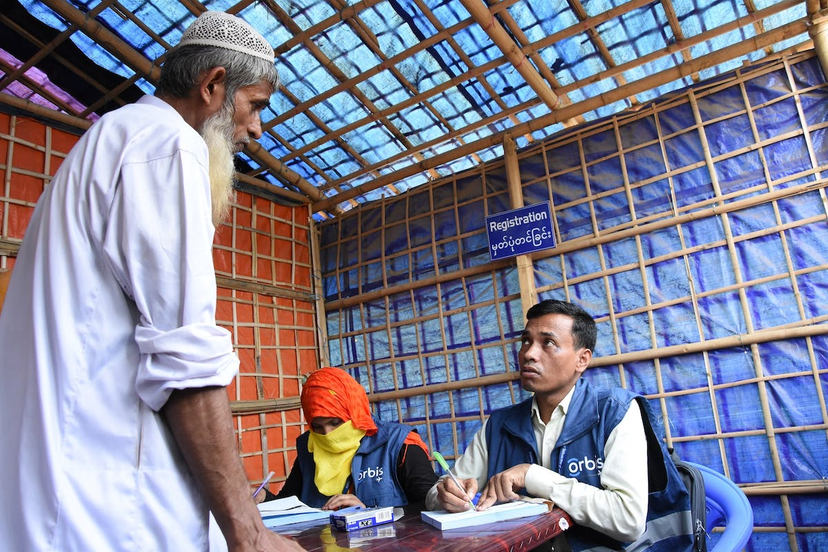 A Rohingya elder discusses his eye problems with an Orbis staff member at a screening in Bangladesh