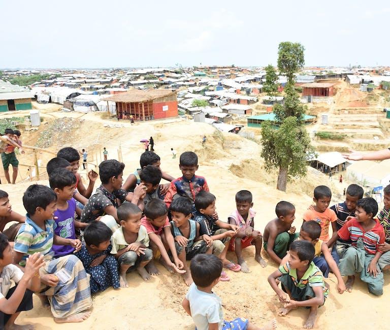 Rohingya children in a refugee camp in Bangladesh wait to be screened