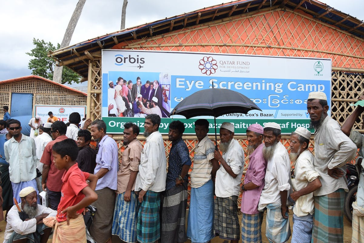 Rohingya people queue outside the Orbis screening centre in Bangladesh