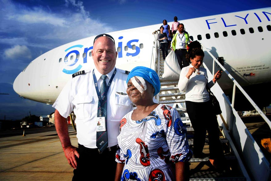 Volunteer Flying Eye Hospital pilot Pete Pitzer escorts a patient down the jet steps in Ghana