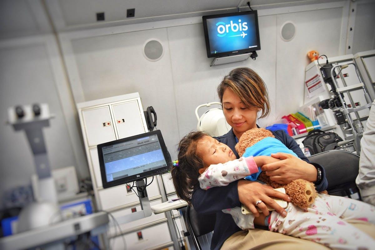 Orbis volunteer with patient on board the Flying Eye Hospital