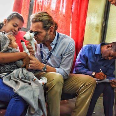 Volunteer Faculty Dr. Daniel Neely screening a baby in Ethiopia