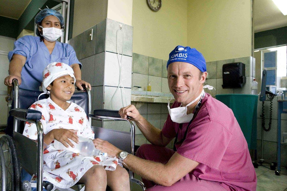 Orbis Volunteer Faculty Dr. Daniel Neely comforts a young patient in Peru in 2011