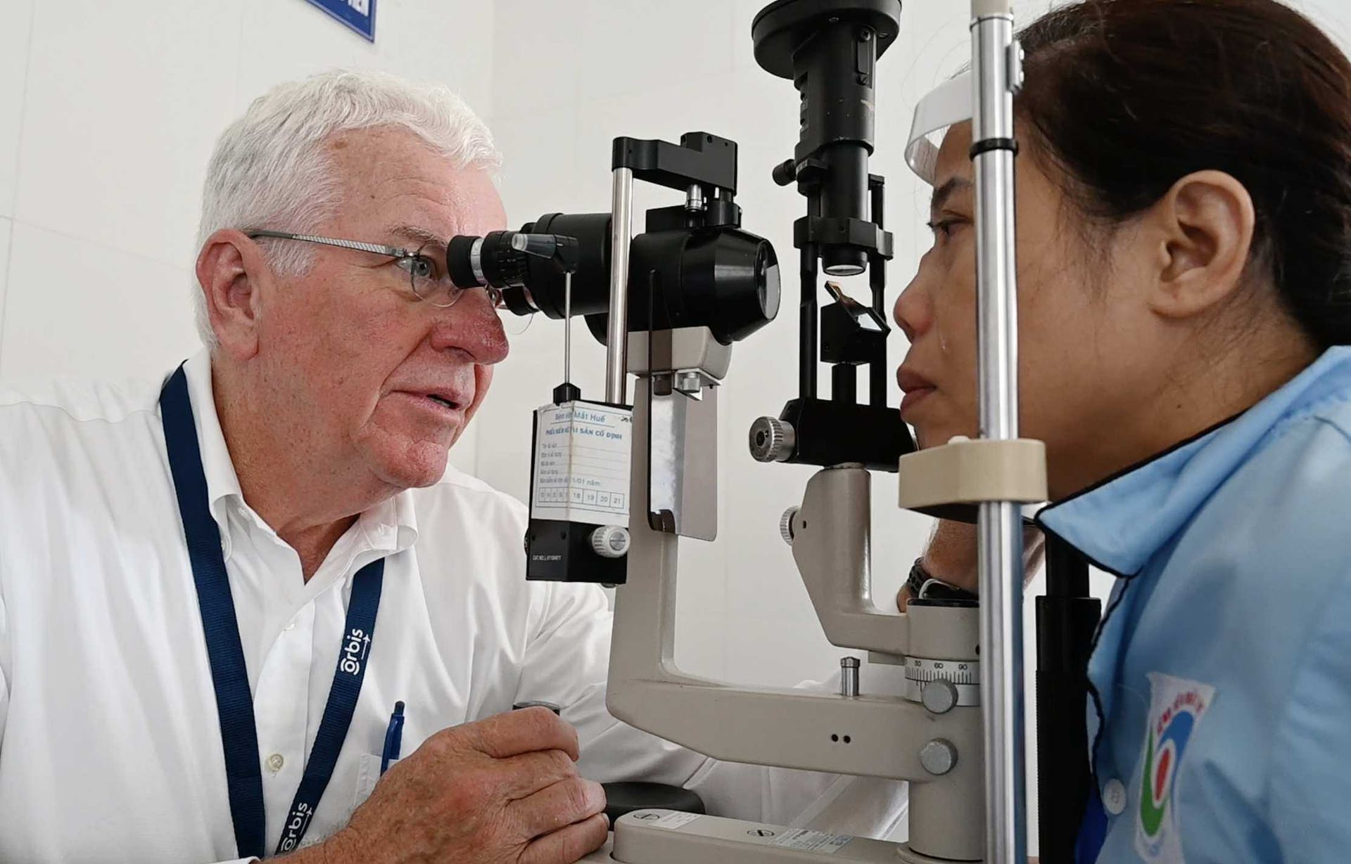 Volunteer Faculty and Glaucoma Specialist Dr. Lee Alward screening a female patient in Hue, Vietnam, 2019