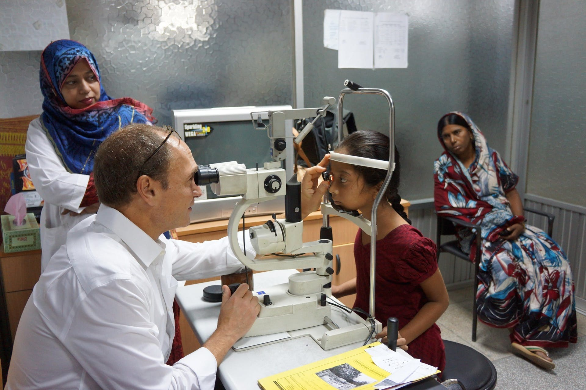 Dr. Peter Kertes screens a child's eyes to check whether they need urgent eye care