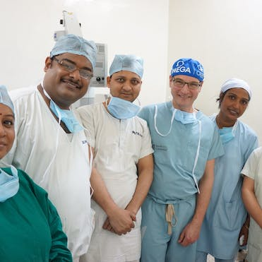 Dr. Peter Kertes pictured with local eye health teams on board the Flying Eye Hospital