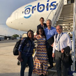 Dr. Peter Kertes pictured with local eye health teams on the steps of the Flying Eye Hospital