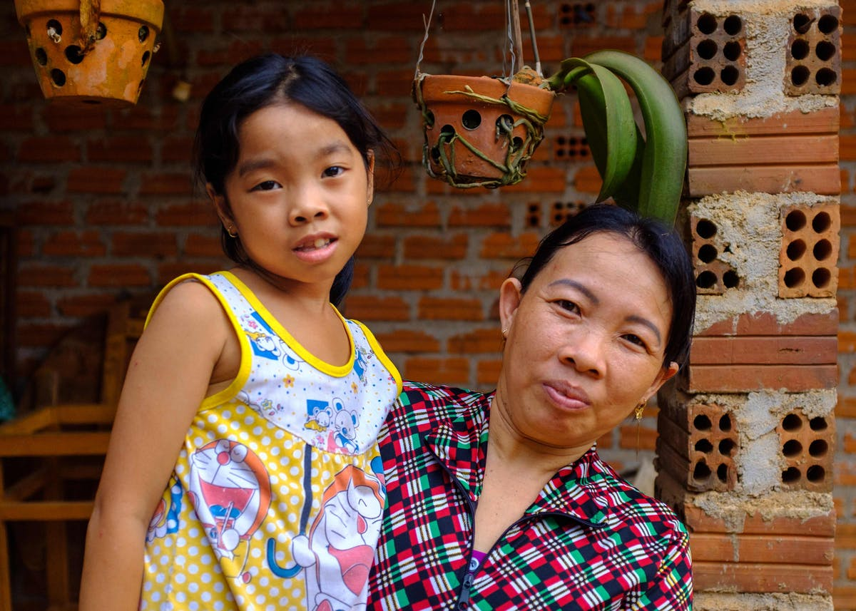 8-year-old strabismus patient Phuong from Vietnam at home with her mother Lan who is delighted her treatment was successful