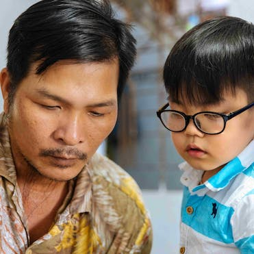 Bilateral cataracts patient Tam from Vietnam with his father.